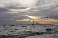 Early evening wind surfer rides the waves as the sunsets. Early evening wind surfing as the sunsets, with an island backdrop royalty free stock images