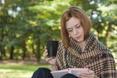 Early fall in the park. Young red-haired woman reading and drinking coffee in the park Stock Photography