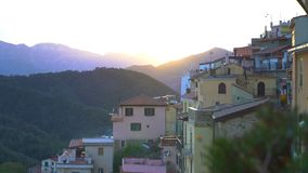 The rising sun illuminates the roofs of a medieval town in the mountains. Early foggy morning in an alpine town. The rising sun illuminates the roofs of a stock video footage