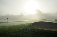 Early golf bunker. Sand bunker with green and flag in early morning mist Royalty Free Stock Images