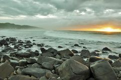 Early morning. Sunrise over Morgans bay's rocky beach Stock Photos