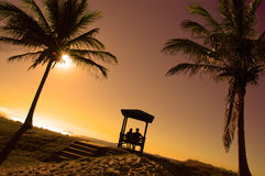 Early morning. A couple relaxing in a rotunda at a  resort looking out at the ocean as the sun rose above the horizon Royalty Free Stock Photos