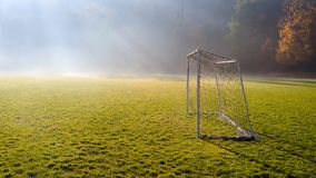Early morning in the amatuer soccer field. Football game playground in autumn foggy morning. Sunlight in the background royalty free stock photography