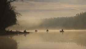 Early morning angling. People fishing in the early morning on the lake Stock Photo