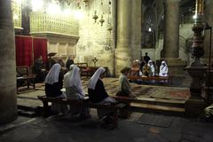 Nuns praying in the Church of the Holy Sepulchre in Jerusalem. Early in the morning before the arrival of pilgrims from around the world, nuns praying in the royalty free stock image