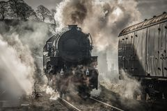 Steam training early morning light. A early morning back lit photograph of a steam train smoking and letting off steam atmospheric image Stock Photos
