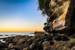 Early morning bather at ocean baths against blue sky and rocky coastline royalty free stock photos