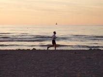 Early morning beach run. Male Jogger running along beach at sunrise stock photo