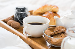 Early morning breakfast. Breakfast in bed with hot coffee and croissants. Healthy breakfast kept on bed. Close up of a cup of tea with cookies on wooden tray in Royalty Free Stock Photo