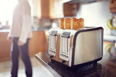 Early morning breakfast toast. Early morning toasted bread, man in the kitchen preparing toast for breakfast at sunrise Stock Photos