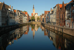 Early morning in Bruges. Beautiful houses typical for Bruges reflecting in the Spiegelrei, one of the canals of Bruges Royalty Free Stock Photo