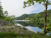 Early morning calm on lac du Kruth-Wildenstein past rock edge Royalty Free Stock Photos
