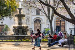 Early morning in central plaza, Antigua, Guatemala. Antigua, Guatemala - March 30, 2018: Early morning vendors, locals & tourists on Good Friday in central plaza royalty free stock photo