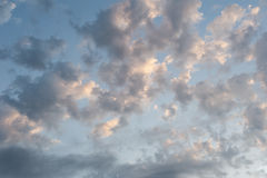 Early morning clouds. Fluffy white clouds against pale blue sky illuminated in early morning royalty free stock photo