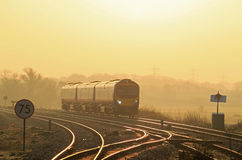 Early morning commuter train at sunrise. Royalty Free Stock Images