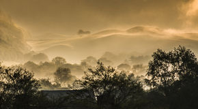 Early morning countryside landscape mist. Beautiful ethereal countryside landscape coming to life as the sun burns of the early dawn morning mist stock image
