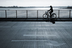 Early morning cyclist. Female cyclist passing a bridge. Motion blur Stock Images