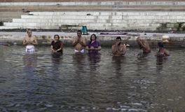 Early Morning Dip in the Ganga. Family and friends take an early morning dip in the Ganges at Varanasi to pray and wash away their sins Royalty Free Stock Image