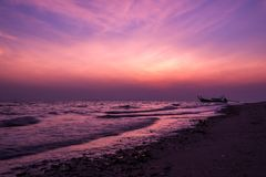 Early morning dramatic violet sky over movement blurred sea and. Beach before sunrise at Laoliang island, Trang province, Thailand Stock Photos