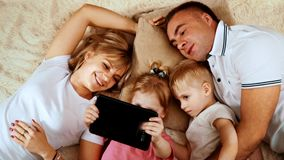 Early morning, the family of Caucasian appearance lying in bed and watching something on the tablet which keeps the girl.  stock video