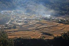 Early Morning Fires Near Rice Paddies, Bhutan. Early morning fires throw a haze across rice paddies in rural, mountainous Bhutan Royalty Free Stock Photo