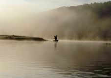 Early Morning Fisherman. Two fishermen on a boat in the fog Stock Images