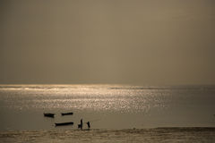 Early morning fishermen. Against the sea shimmering in the sunrise in Mombassa Royalty Free Stock Images
