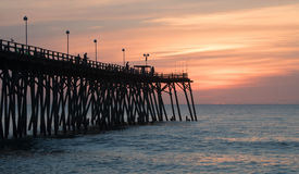Early Morning Fishermen. The sky lightens in the east as the fishermen cast their lures from the Kure Beach Pier Royalty Free Stock Photography