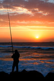 Early morning fishing. A man fishing on beach at sunrise near a pier in early morning with sun lights reflect on ocean water and rock Royalty Free Stock Photography