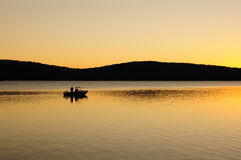 Early morning fishing boat on a lake at dawn Royalty Free Stock Photos