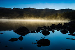 Early morning fog glowing white on a lake. Mist glowing white on a lake at sunrise Royalty Free Stock Images