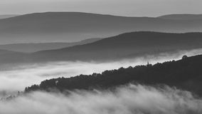 Early morning fog and mist between rolling hills in the Scottish Highlands Stock Images
