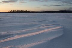 Early morning on the frozen snow-covered lake. Ripples in the snow after the wind. Orange dawn