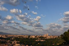 Early Morning Hot air balloons over Segovia, Spain. Dawn hot air balloons sailing over morning sunlit city of Segovia Spain royalty free stock image