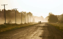 Early morning jog. Two people - one jogging, one riding bicycle in the early morning mist on a country road Stock Photography