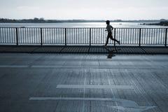 Early morning jogger. Female jogger passing a bridge. Motion blur Stock Photo
