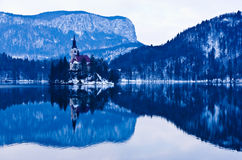 Early morning on the lake Bled and reflection of a church on small island Royalty Free Stock Photo