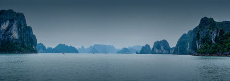 Early morning landscape with blue fog and tourist junks floating Royalty Free Stock Photos