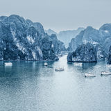 Early morning landscape with blue fog and tourist junks floating Royalty Free Stock Photography