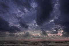 At the beach; early morning, landscape with large clouds away, and storm Royalty Free Stock Images