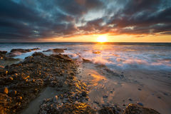 Early morning landscape of ocean over rocky shore and glowing su Royalty Free Stock Photography