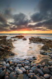 Early morning landscape of ocean over rocky shore and glowing su Royalty Free Stock Photo
