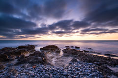 Early morning landscape of ocean over rocky shore and glowing su Royalty Free Stock Photos
