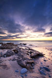 Early morning landscape of ocean over rocky shore and glowing su Stock Photography