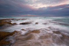 Early morning landscape of ocean over rocky shore and glowing sunrise stock images