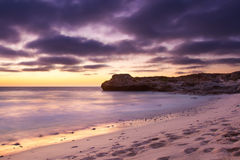 Early morning landscape of ocean over rocky shore and glowing su Stock Photo