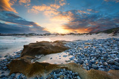Early morning landscape of ocean over rocky shore and glowing sunrise stock photos