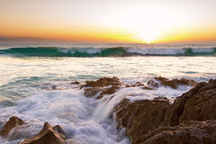 Early morning landscape of ocean over rocky shore and glowing Royalty Free Stock Image