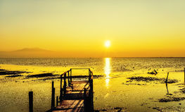 Early morning, magic sunrise over sea. Long exposure of magic sunrise over the ocean with and a wooden bridge Stock Photo