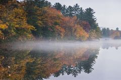 Mist hovers along a lake reflecting a New England autumn. royalty free stock images
